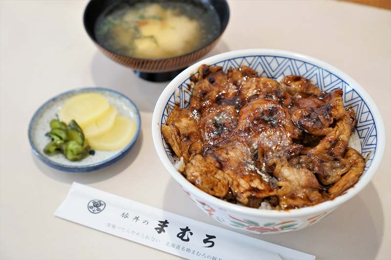 豚丼のまむろの豚丼や味噌汁がテーブルに置かれている