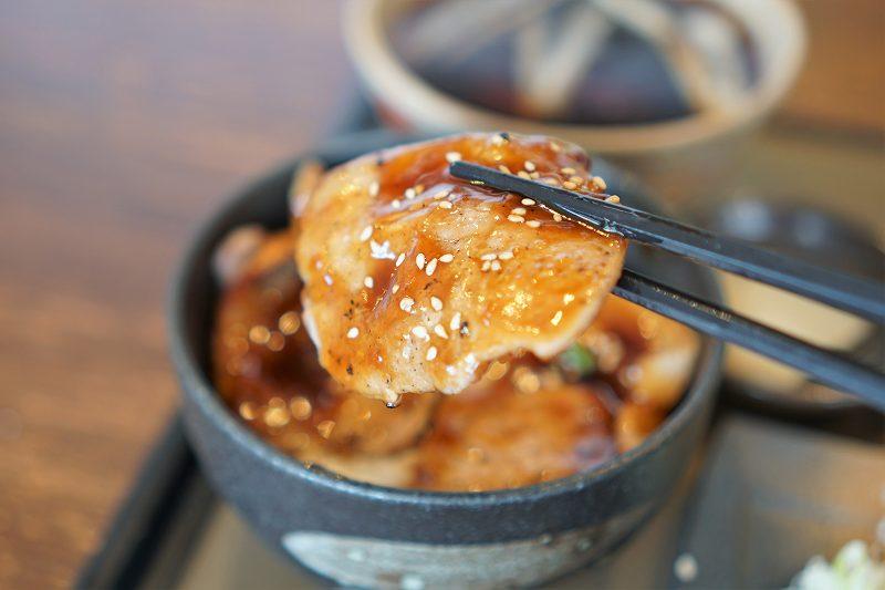 蕎麦さとやまの豚丼の豚肉を箸で持ちあげている様子