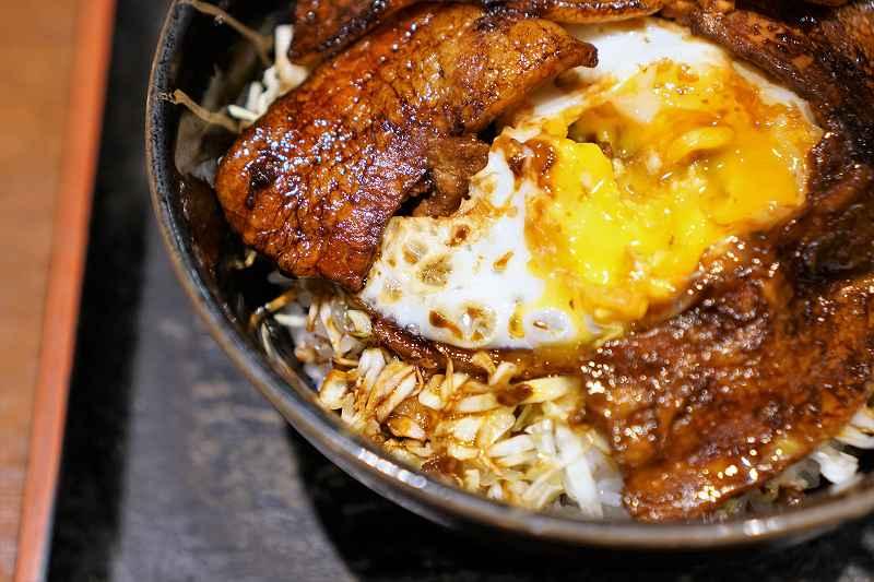 キャベツの千切りと卵がトッピングされた豚玉丼がテーブルに置かれている