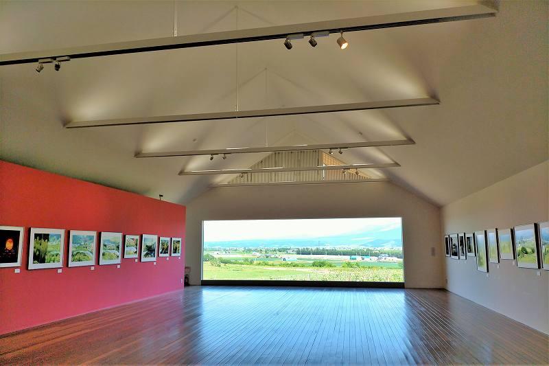 正面に大きな窓があるギャラリー「神々の遊ぶ庭」の内観