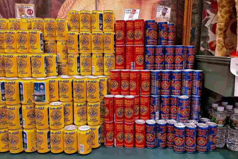 ラッキーピエロのオリジナル缶ドリンクが棚に積まれている