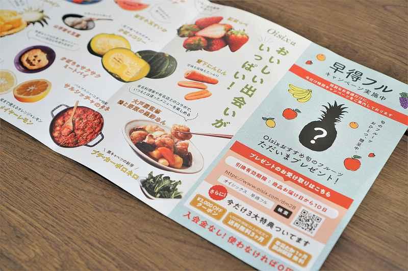 Oisixのフルーツや野菜の写真がのったダイレクトメールがテーブルに置かれている