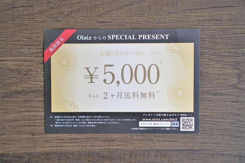 Oisixのお買い物クーポン5000円がテーブルに置かれている