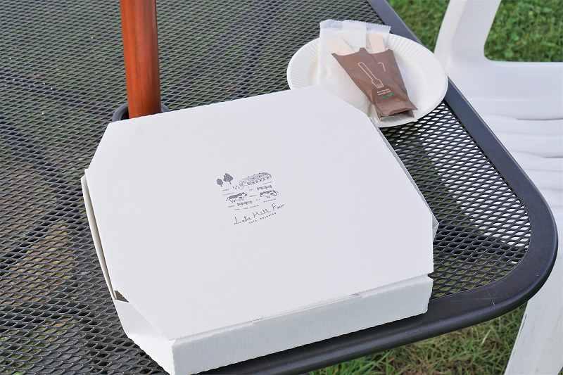 ピザの箱と紙皿などがテーブルに置かれている