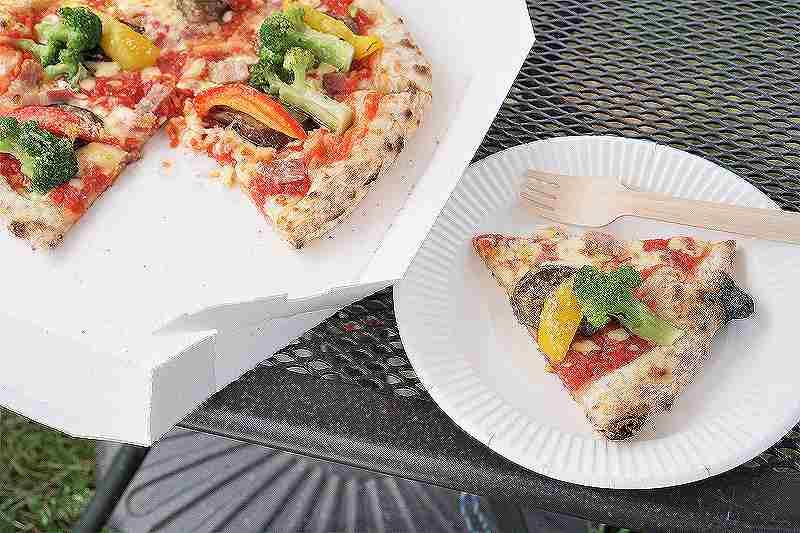 紙皿に取り分けられた夏野菜のピザがテーブルに置かれている
