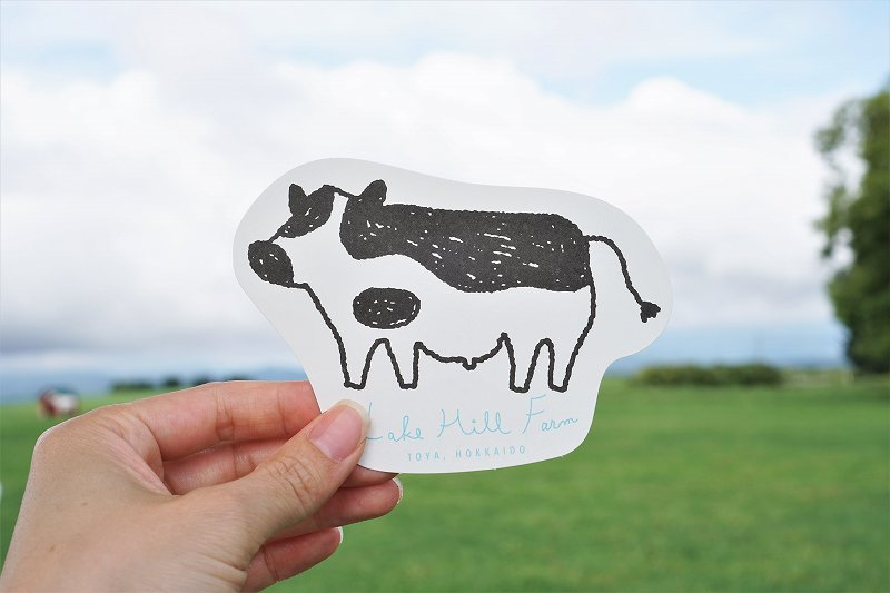 牛のイラストが描かれたレークヒルファームのショップカードを手に持っている様子