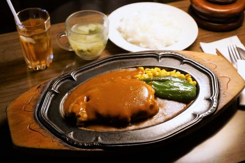 鉄板にのせられたポークチャップやご飯がテーブルに置かれている