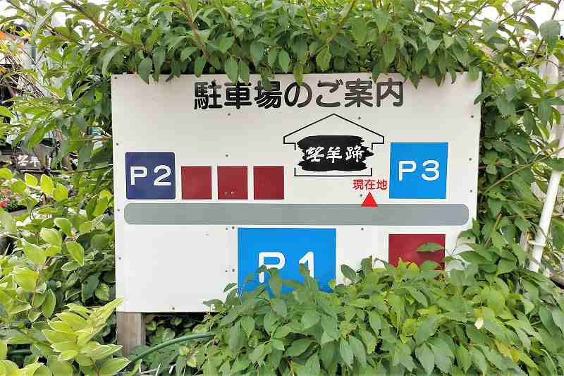 望羊蹄の駐車場案内版が緑の中に立てられている