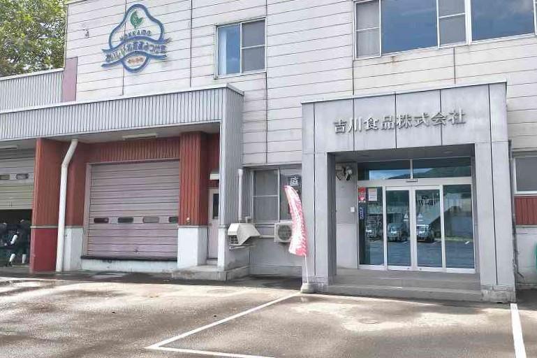 白を基調とした吉川食品株式会社の外観